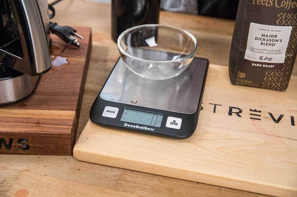 An empty glass bowl rests atop a precision scale.
