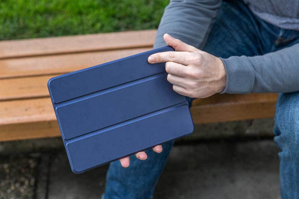 A person in a long sleeved blue shirt holds a tablet with a blue cover while sitting on a park bendch.