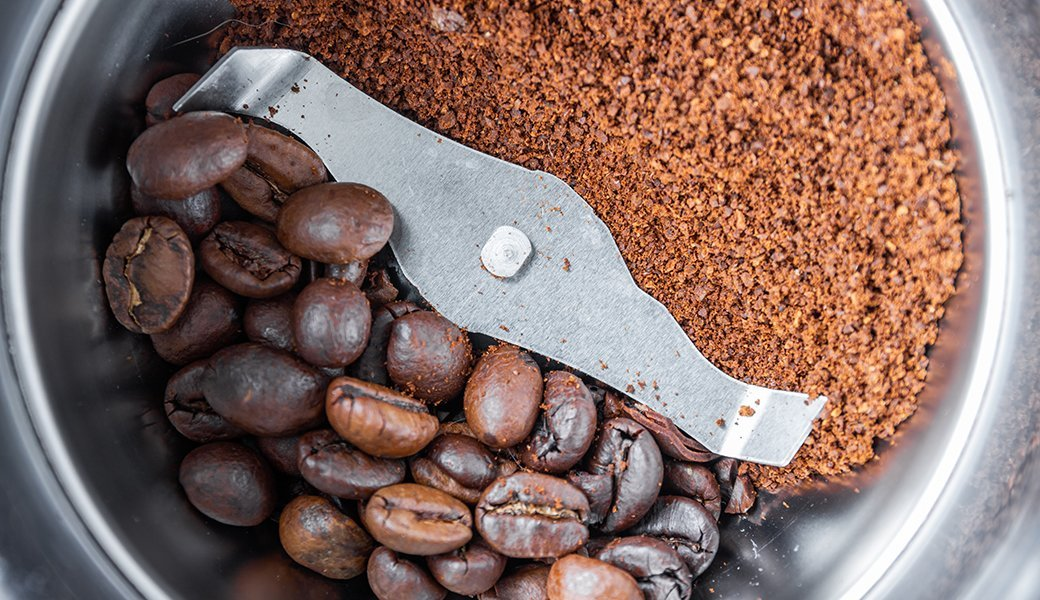 A coffee grinder contains half whole and half ground coffee beans