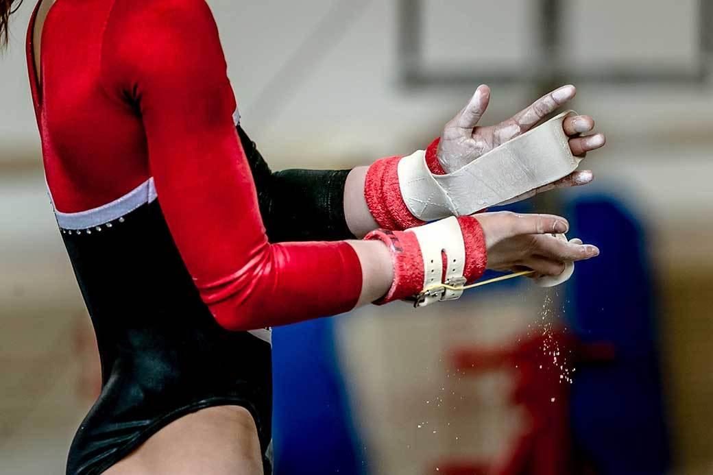 A gymnast wearing hand grips chalks their hands.