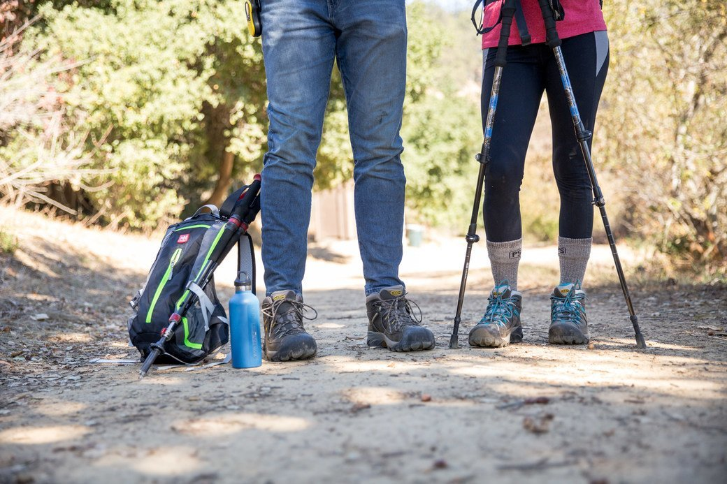Two people, one wearing jeans and the other wearing black leggings, pause for a rest while hiking.